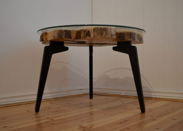 Natural edge wooden slab coffee table with three modern, black legs and round glass top.