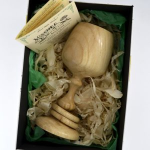 Wooden goblet with two captive rings around stem in lidded presentation box with wood shavings, green tissue paper, and an information card