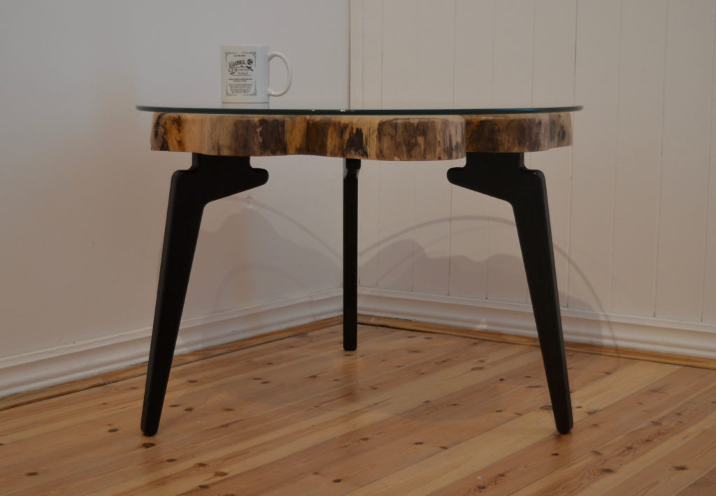 Natural/live edge modern wood slab coffee table with round glass top, 3 black legs, and Magill Woodcraft Ireland cup on table top.