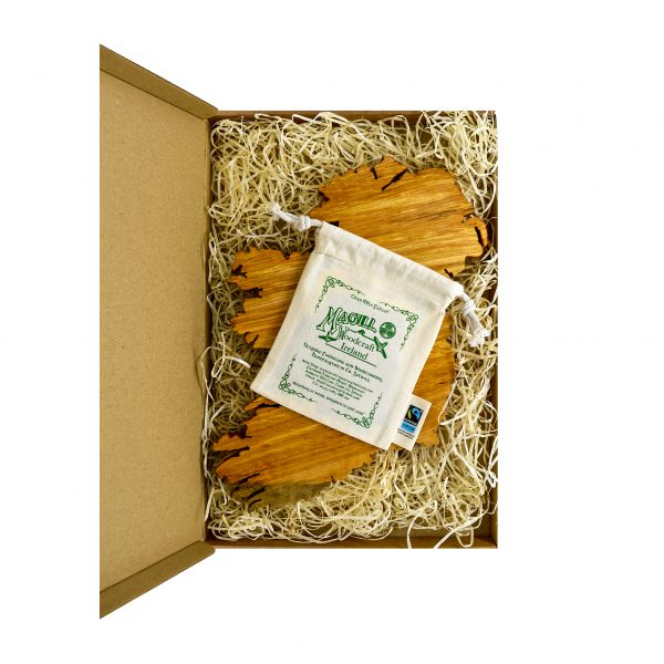 Wooden map of Ireland with a screen-printed cotton bag on top, in a cardboard gift box with wooden shavings as packaging.