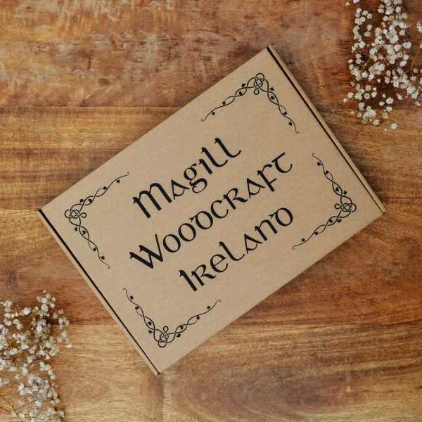Lidded cardboard gift box with Magill Woodcraft Ireland Irish font printed on a wooden table. For wooden map of Ireland product.