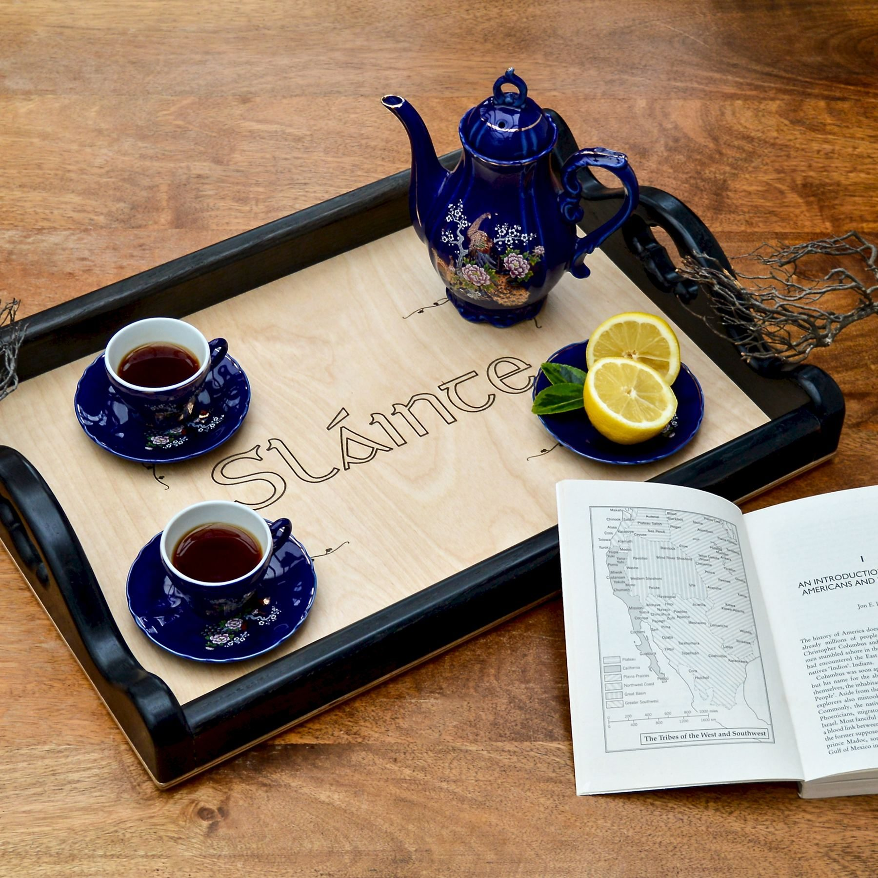 Hanmade wooden tray engraved with the Irish word Sláinte. Two blue cups and a Japanese tea pot on top.