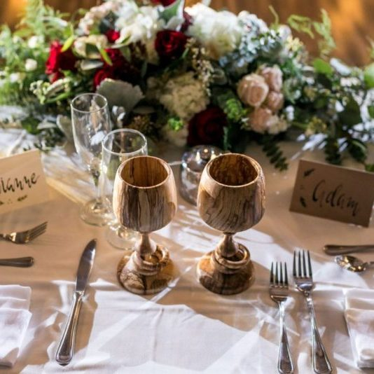 Wooden wedding goblets on white table cloth with flowers in background