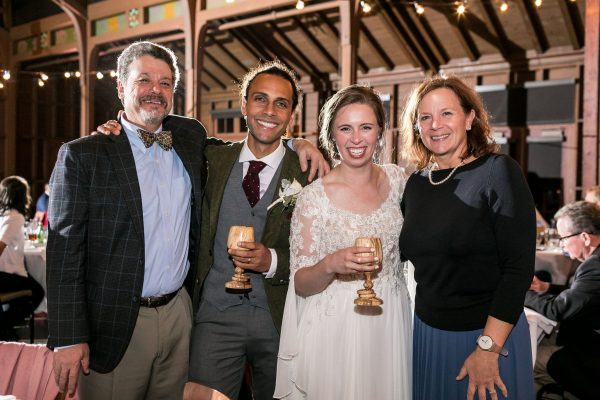 Couple at their wedding holding wooden goblets with smiles on their faces.